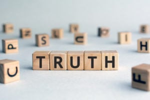 Truth - word from wooden blocks with letters, real facts truth concept, random letters around, white background